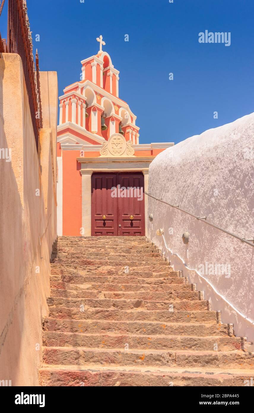 En regardant les marches en pierre qui mènent aux portes de la cour de l'église et le clocher coloré au-dessus, à Fira, sur l'île grecque de Santorin Banque D'Images