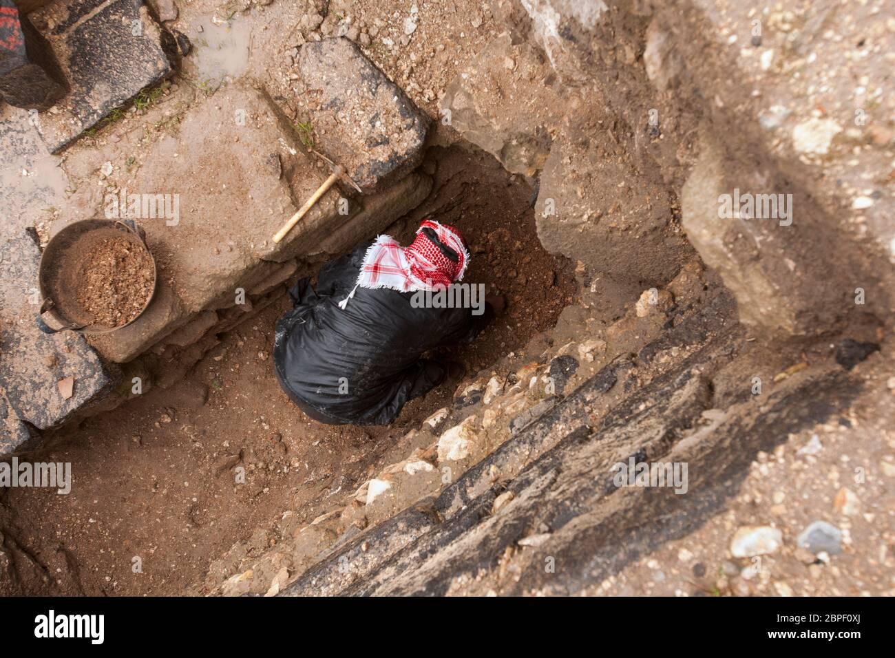 Un jordanien portant des héaddres de shemagh keffiyeh à carreaux rouges et blancs travaillant dans un site archéologique de l'ancienne Gadara ou Gedaris également connu sous le nom d'Umm Qais ou Qays dans le nord-ouest de la Jordanie Banque D'Images