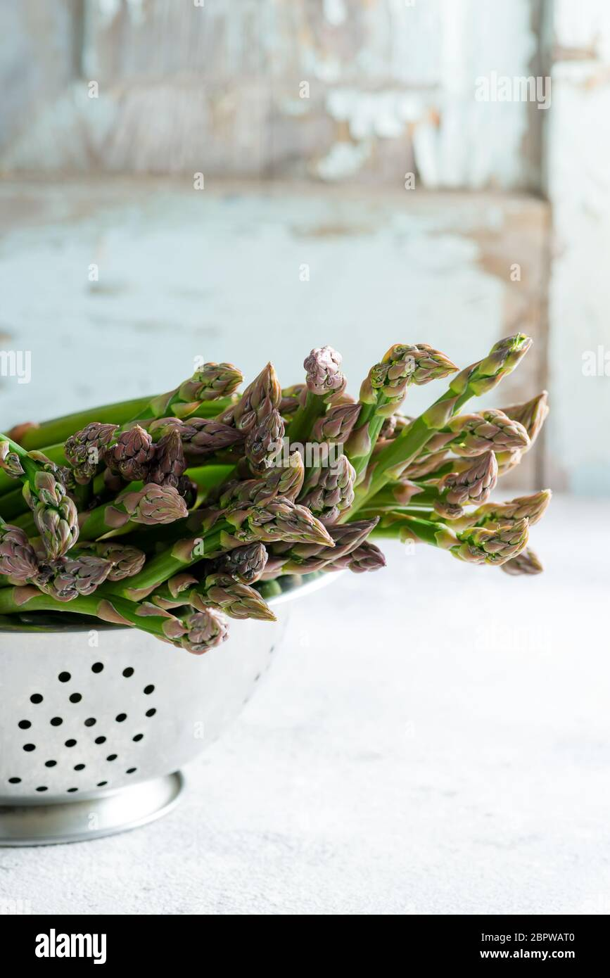 Asperges biologiques crues dans une passoire prête à cuire des aliments végétariens sains sur un fond de marbre gris clair. Banque D'Images