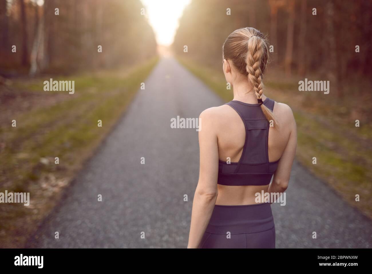 Jeune femme sportive en bonne santé marchant au lever du soleil le long d'une route rurale à travers une forêt dense vers la lueur du soleil à la fin entre les arbres dans un Banque D'Images