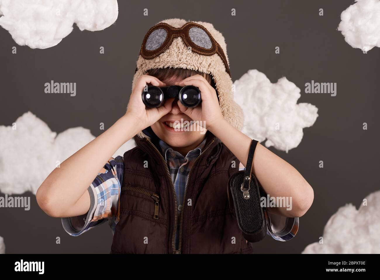 un garçon joue avec des jumelles et rêve de devenir pilote, habillé dans une veste rétro et un casque avec des lunettes, des nuages de laine de coton, un dos gris Banque D'Images
