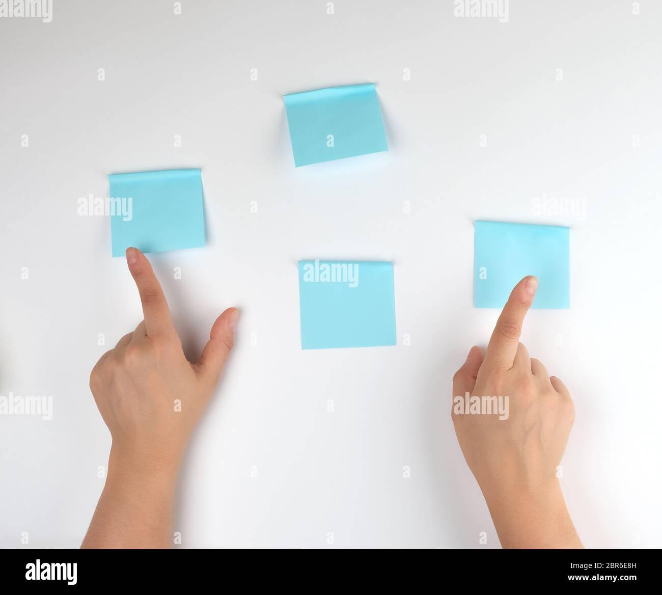 Beaucoup d'autocollants bleu sur un fond blanc et deux femmes mains pointant sur eux, contexte conceptuel Banque D'Images