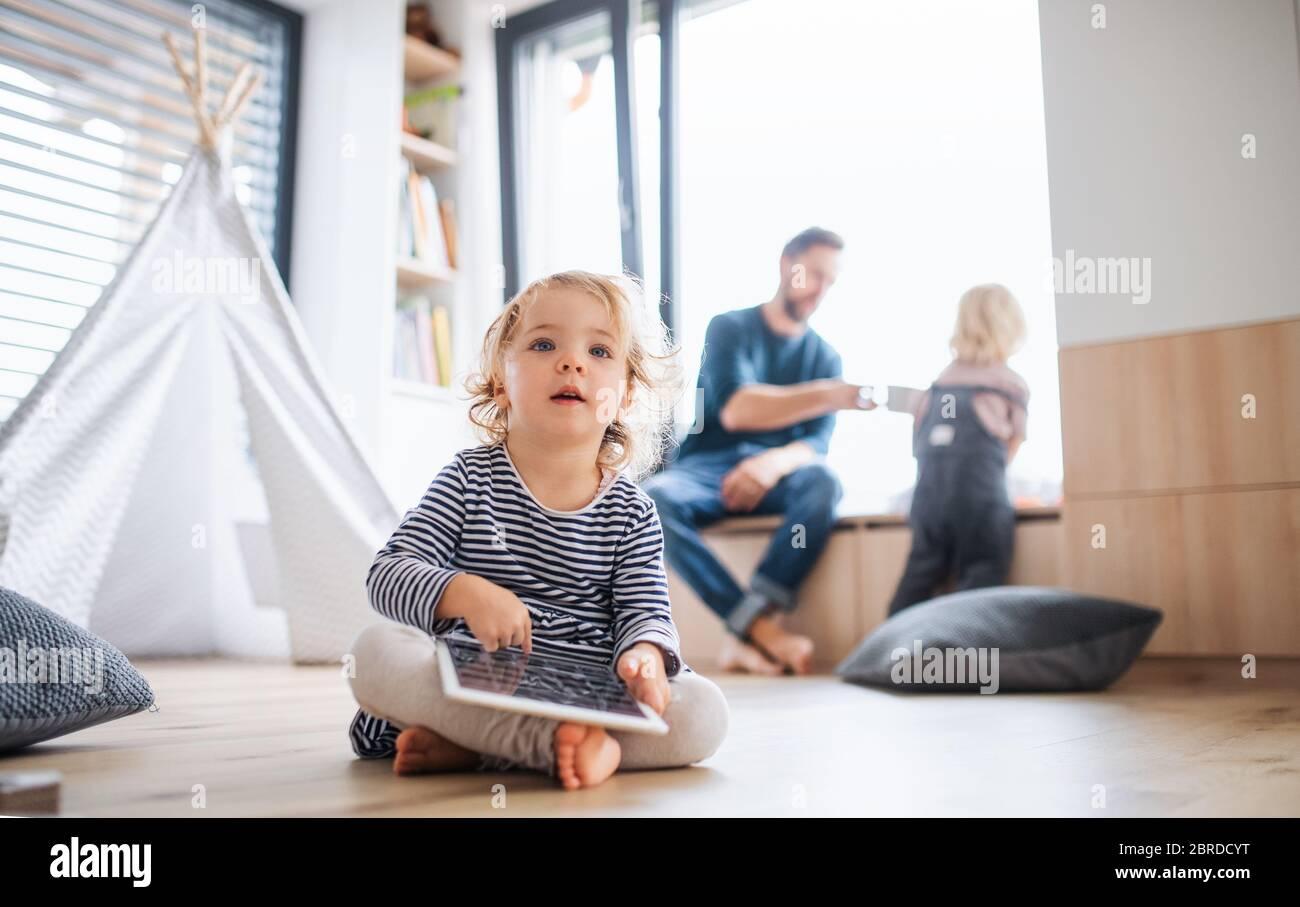 Petite fille assise à l'intérieur dans la chambre, avec une tablette. Banque D'Images