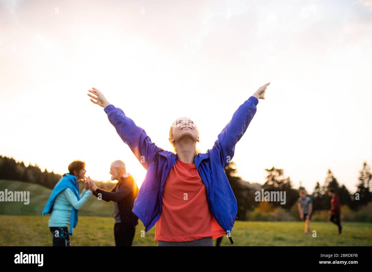 Un portrait de jeune femme avec un grand groupe de personnes faisant de l'exercice dans la nature. Banque D'Images