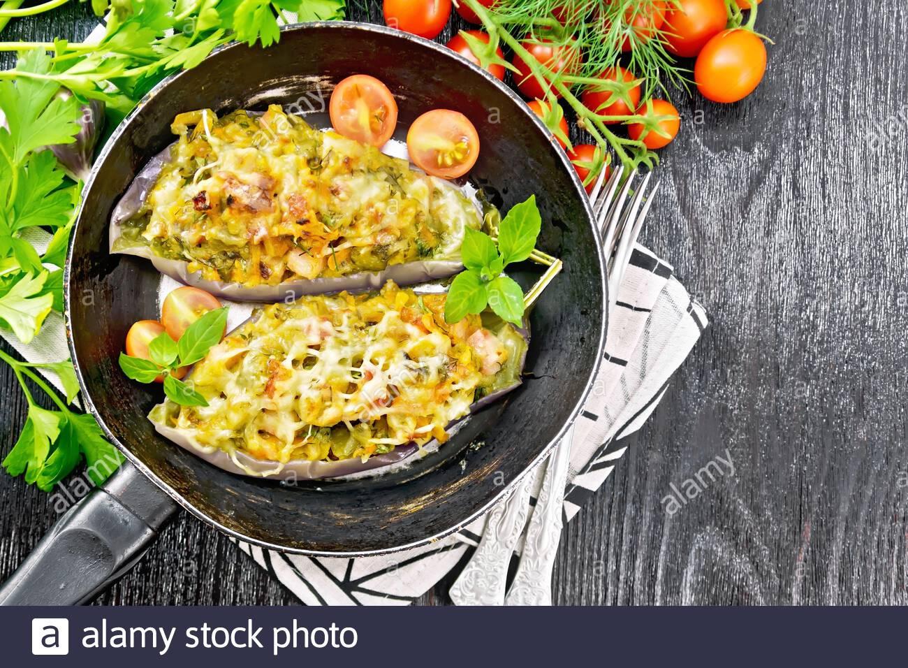 Aubergines farcies avec poitrine fumé, tomates, oignons, carottes à l'ail, le fromage et les herbes dans une casserole sur une serviette sur le haut conseil en bois noir Banque D'Images
