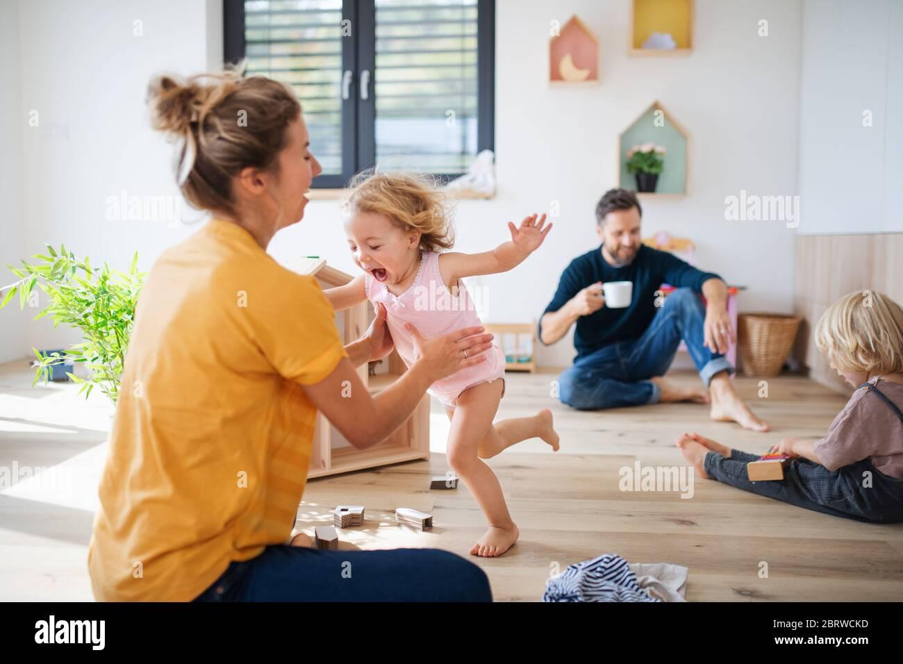 Jeune famille avec deux petits enfants à l'intérieur dans la chambre à coucher jouant. Banque D'Images