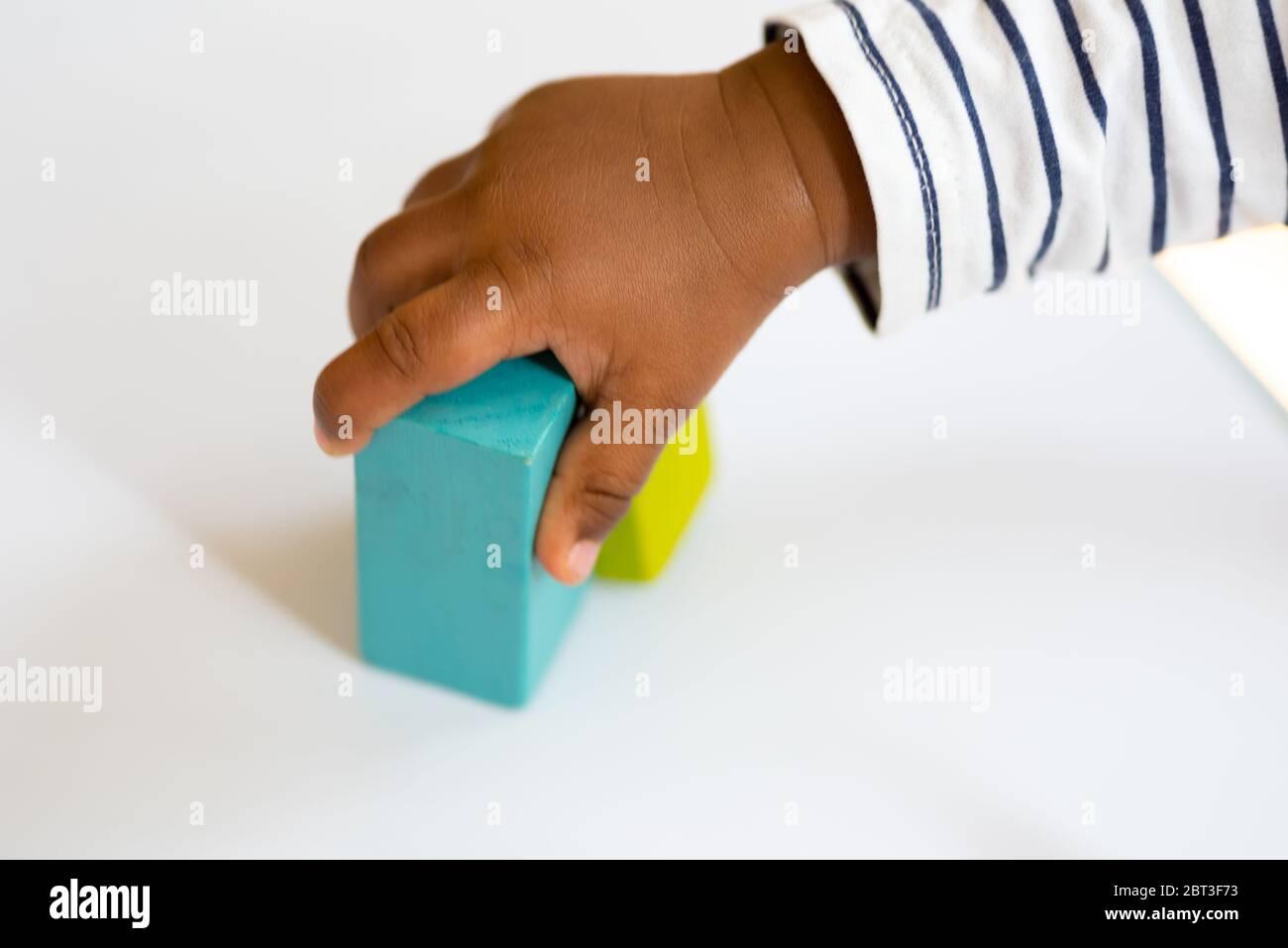 Un enfant d'un an jouant avec des blocs de bois de construction colorés sur la table Banque D'Images