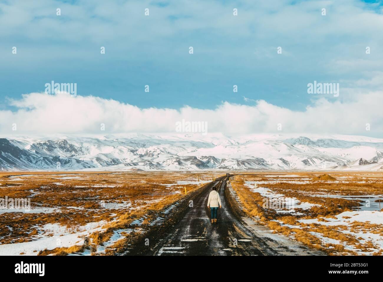 Femme marchant le long d'une route vide en hiver, Islande Banque D'Images