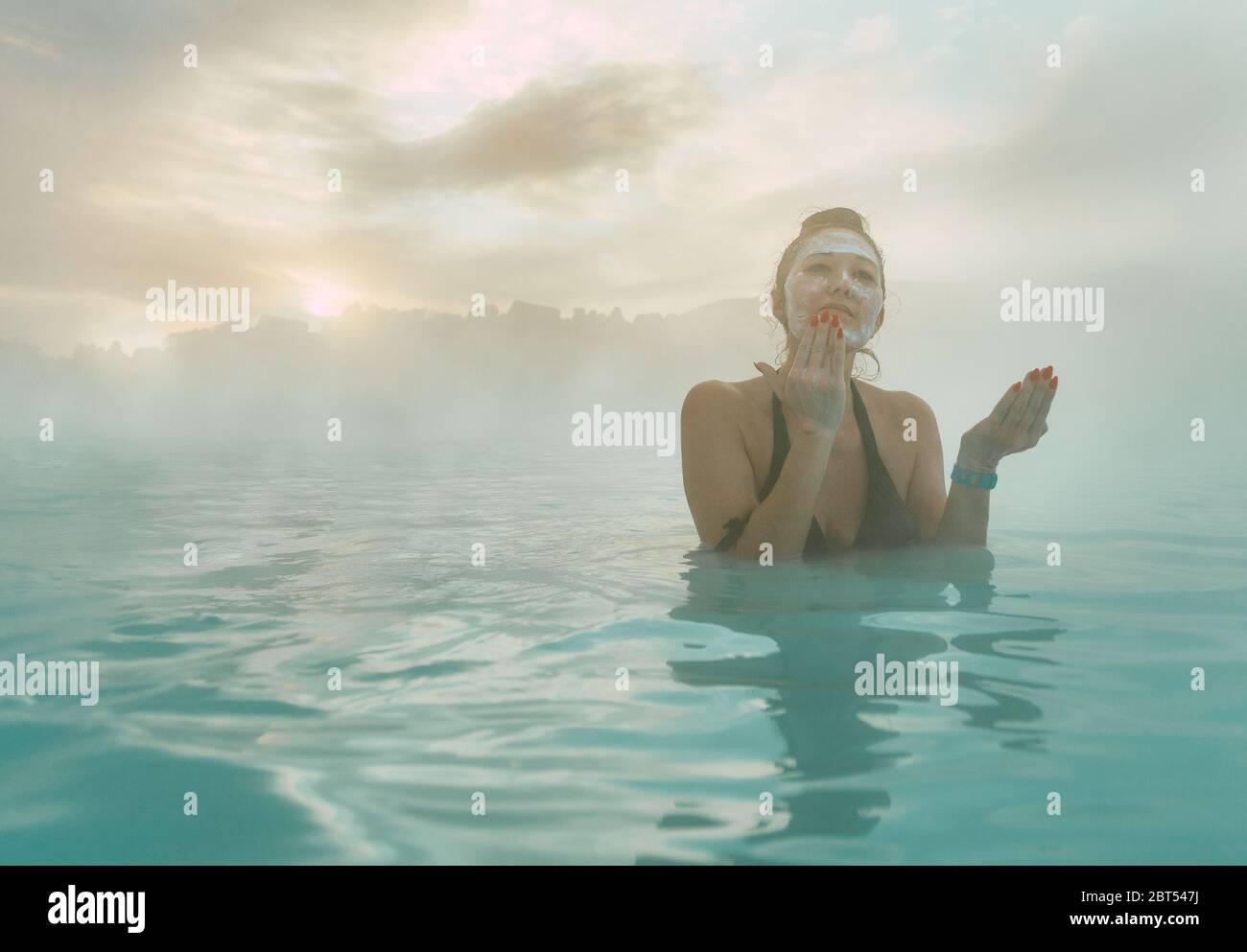 Femme debout dans le Blue Lagoon mettant de la boue sur son visage, Islande Banque D'Images