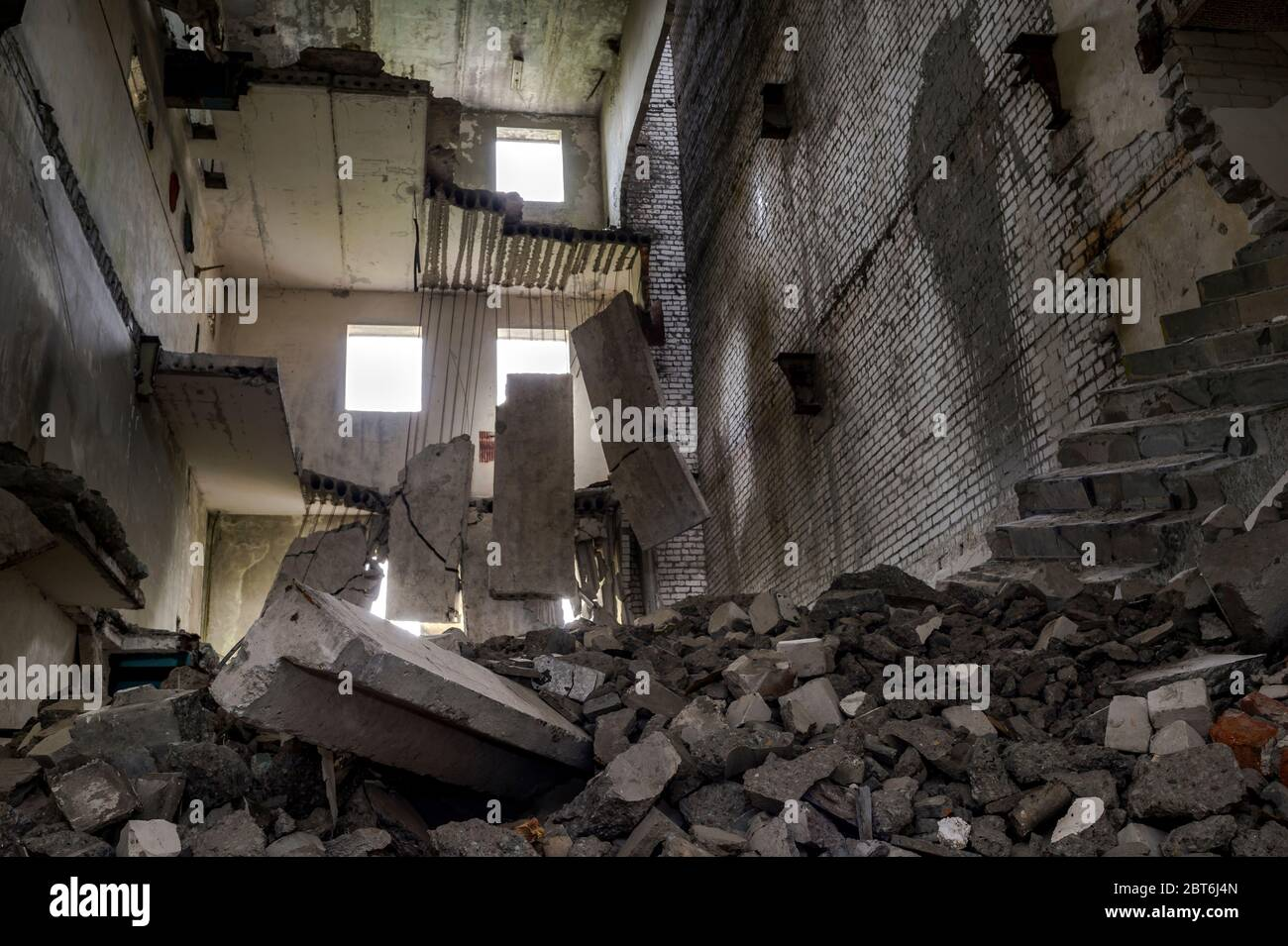 Bâtiment en béton détruit à l'intérieur avec une pile de débris de construction au premier plan et d'énormes dalles de béton suspendues sur l'armature contre le mur arrière Banque D'Images