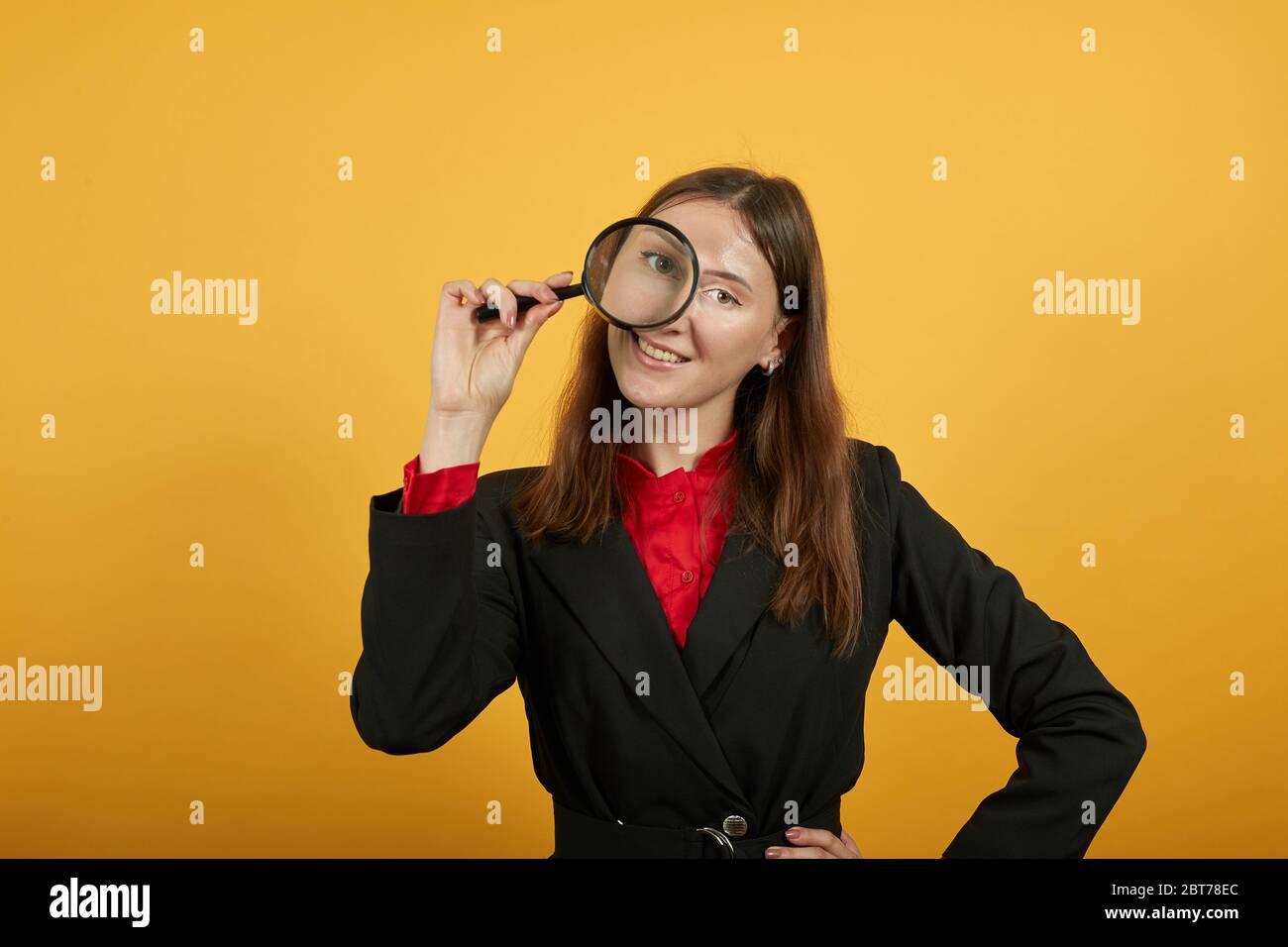 Femme souriante tient la loupe à la main et regarde avec l'œil. Scientifique Banque D'Images