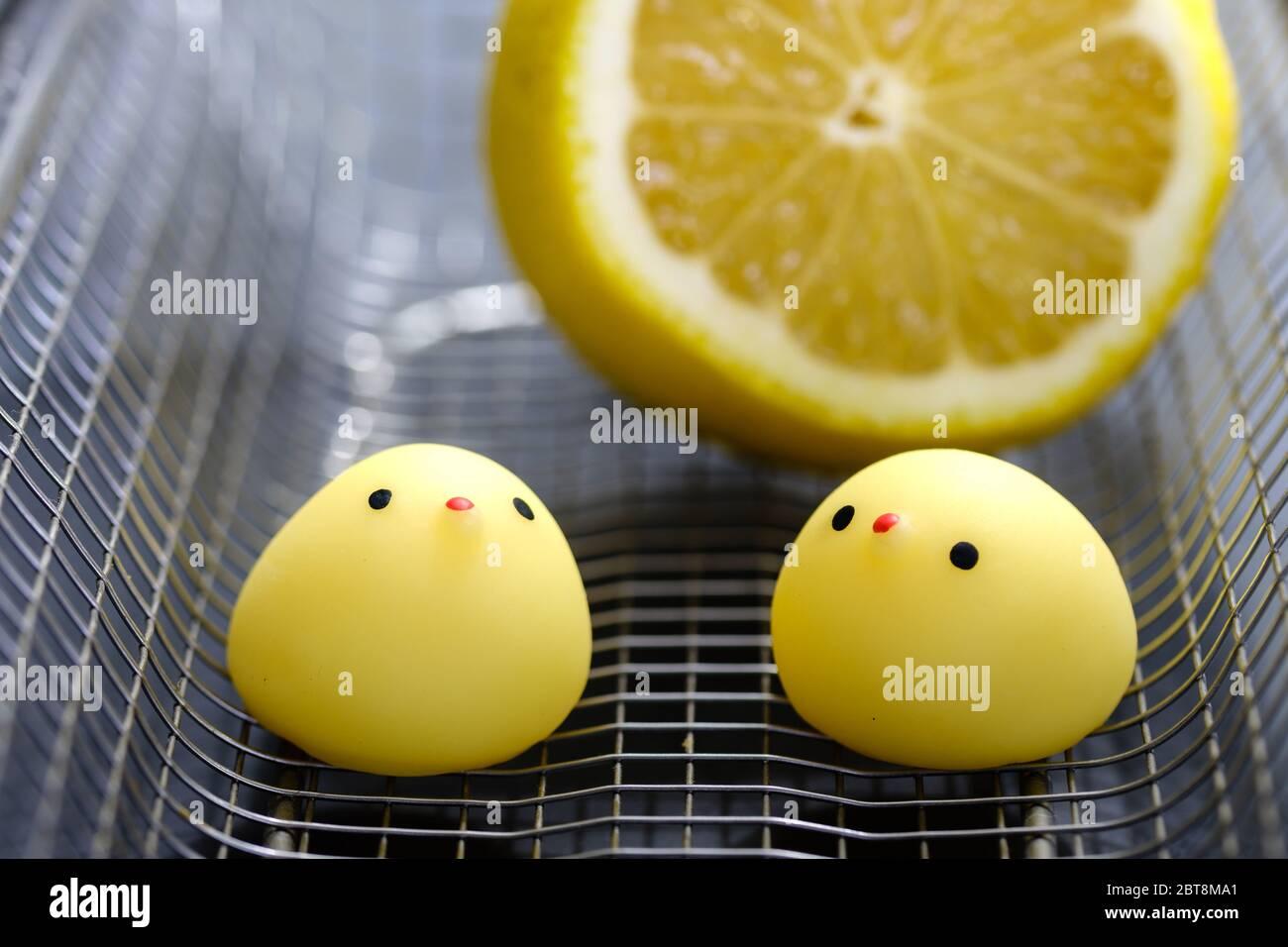 jouet de poulet avec citron dans un panier en métal Banque D'Images