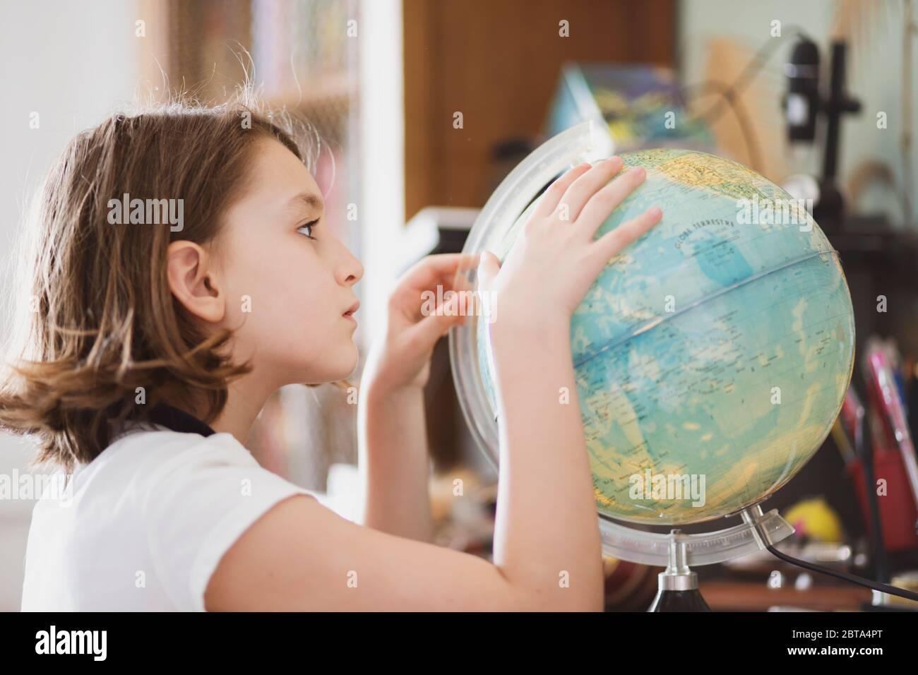 Une jeune fille qui sime à son bureau et regarde un globe. Banque D'Images