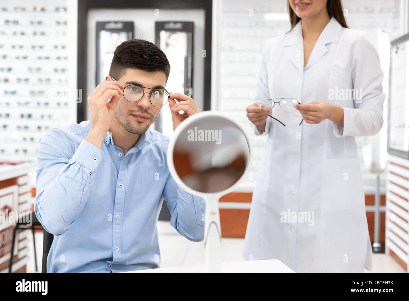 Spécialiste aidant un jeune homme à choisir des lunettes Banque D'Images