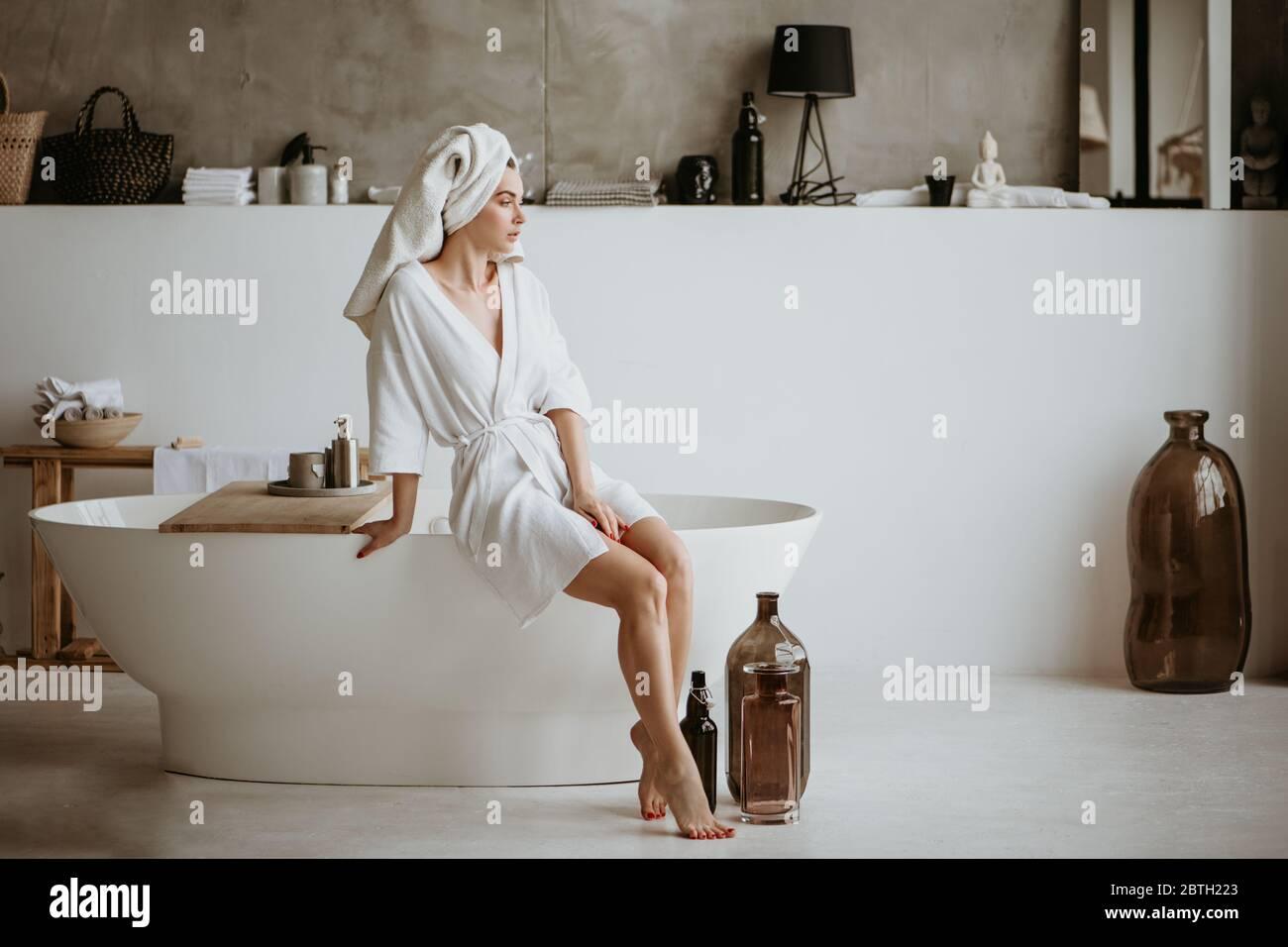 Belle jeune femme en peignoir assis sur le bord de la baignoire. Banque D'Images
