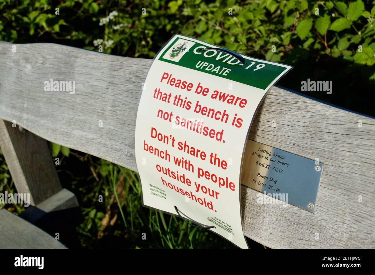 Un panneau d'avertissement Covid-19 sur un banc à Wimbledon Common, Londres, Royaume-Uni Banque D'Images