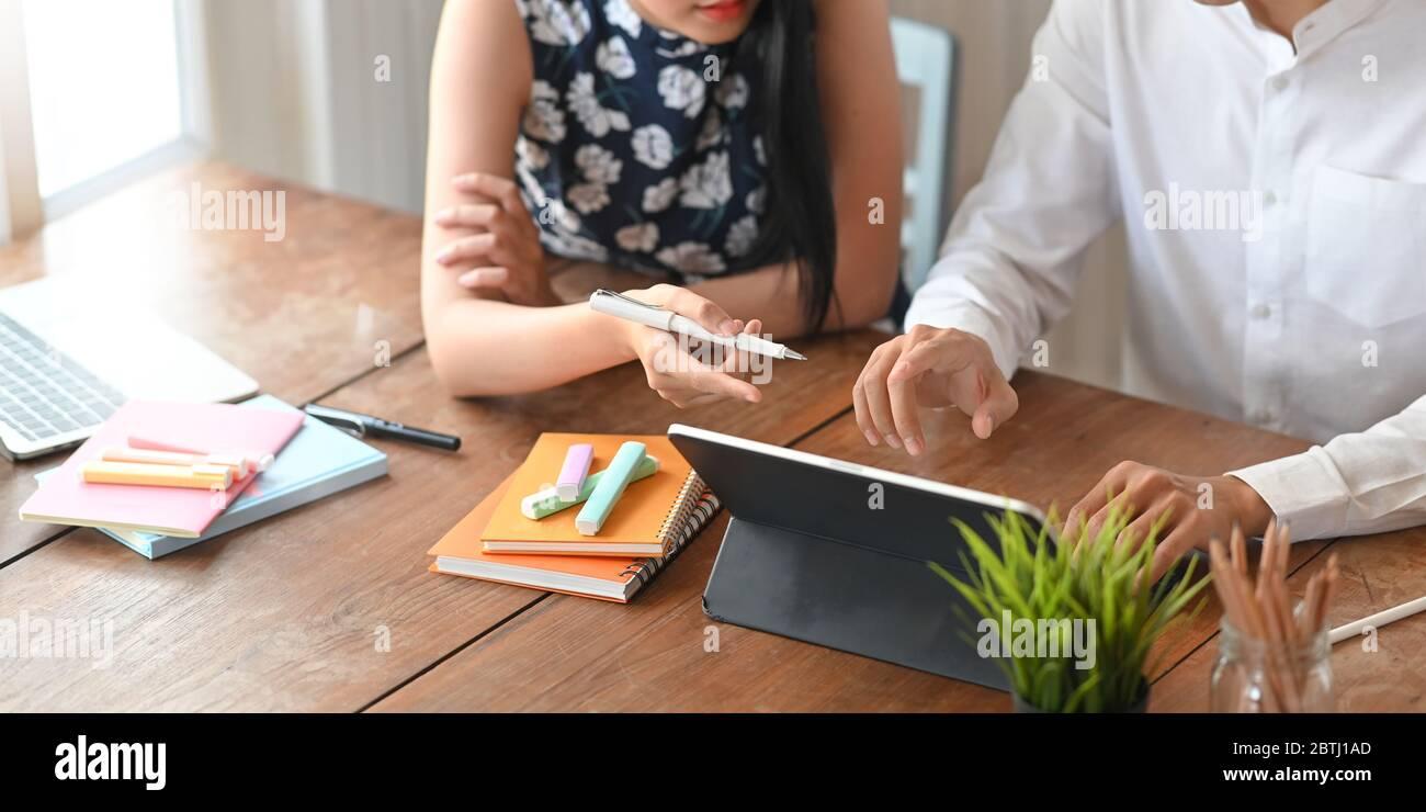 Image rognée de l'équipe de développement d'entreprise travaillant avec une tablette et une note d'ordinateur tout en étant assis sur le bureau de travail en bois pour un travail confortable Banque D'Images
