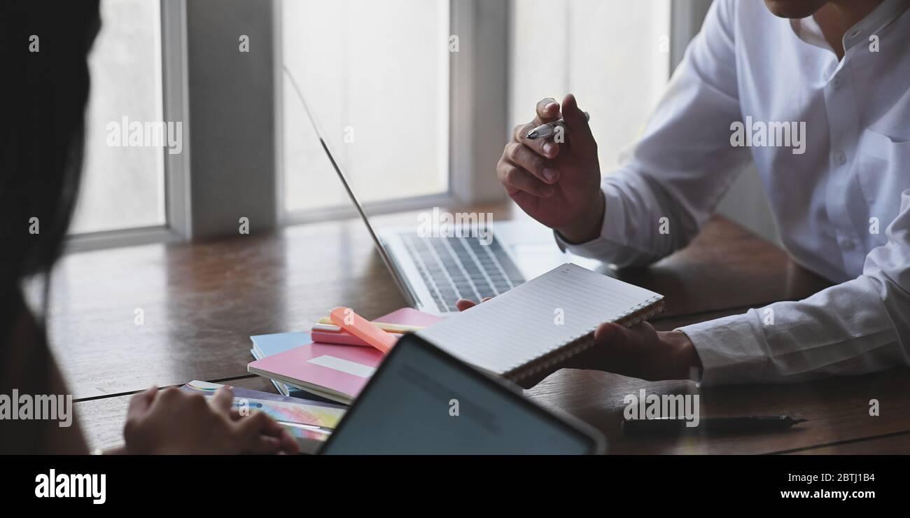 Image rognée d'un homme d'affaires prenant des notes en étant assis devant un ordinateur portable et de son collègue au bureau en bois sur le salon gagne Banque D'Images
