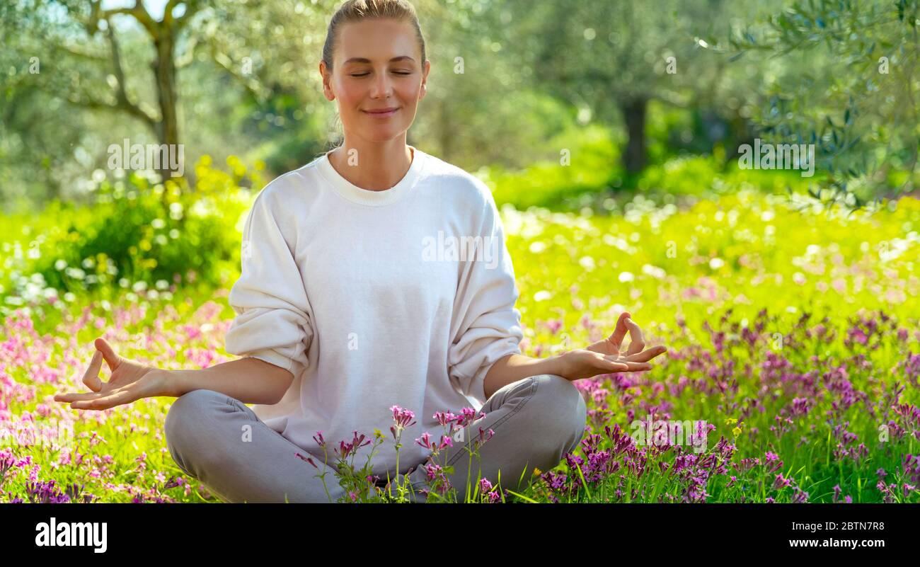 Belle fille calme avec les yeux fermés méditant dans le jardin frais en fleurs, l'unité avec la nature, l'équilibre zen, un mode de vie sain heureux Banque D'Images