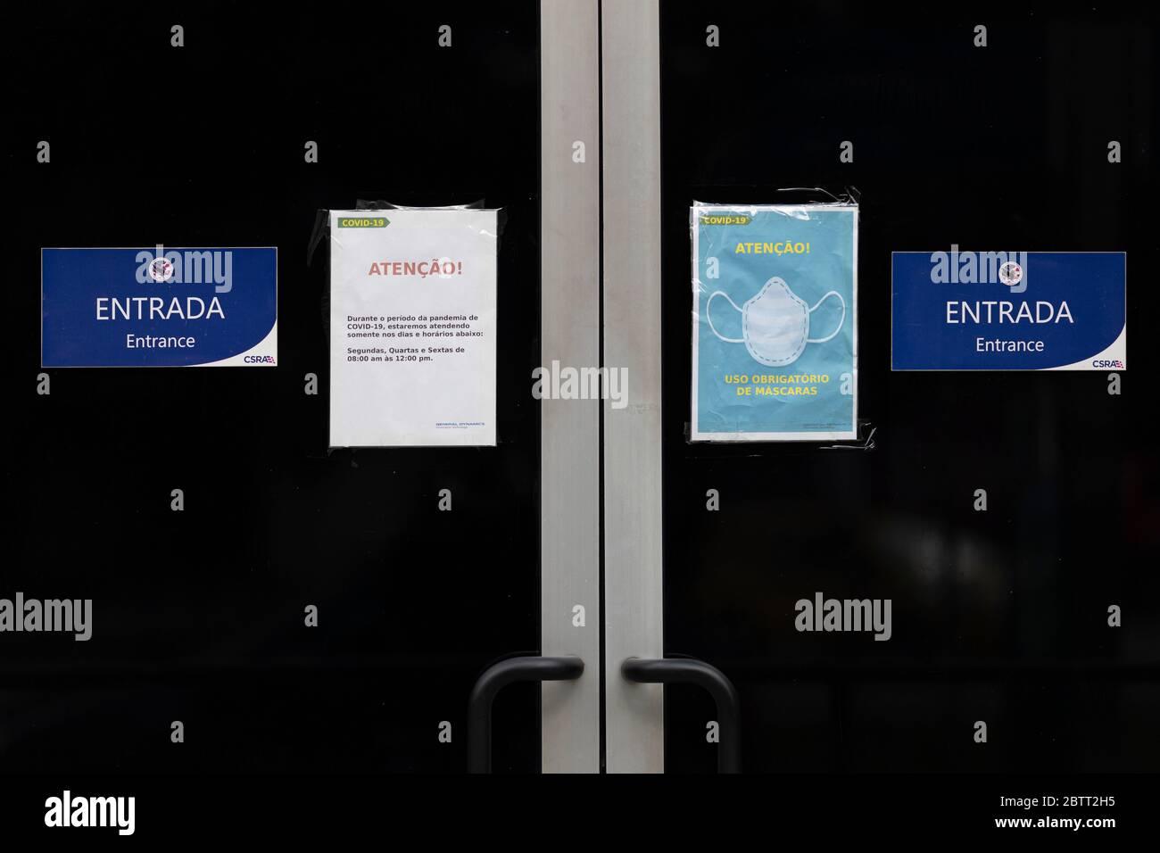Panneau de notification sur la porte d'entrée du centre de demande de visa des États-Unis à Rio montrant un masque facial. TRADUCTION : ATTENTION. UTILISATION OBLIGATOIRE DES MASQUES. Banque D'Images