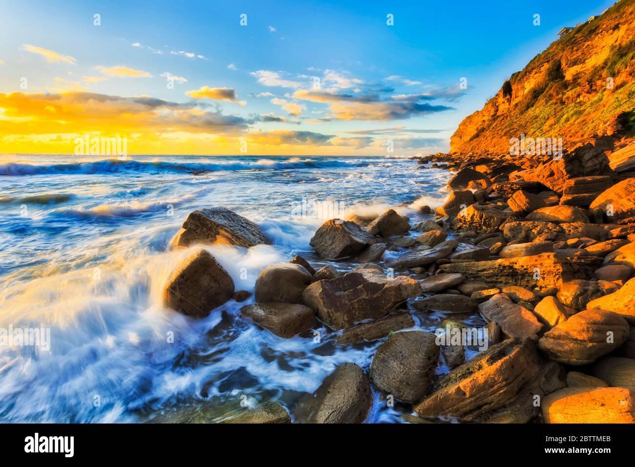 Rochers de grès sous promontoire à Bungan plage des plages du nord de Sydney dans la douce lumière du matin. Banque D'Images