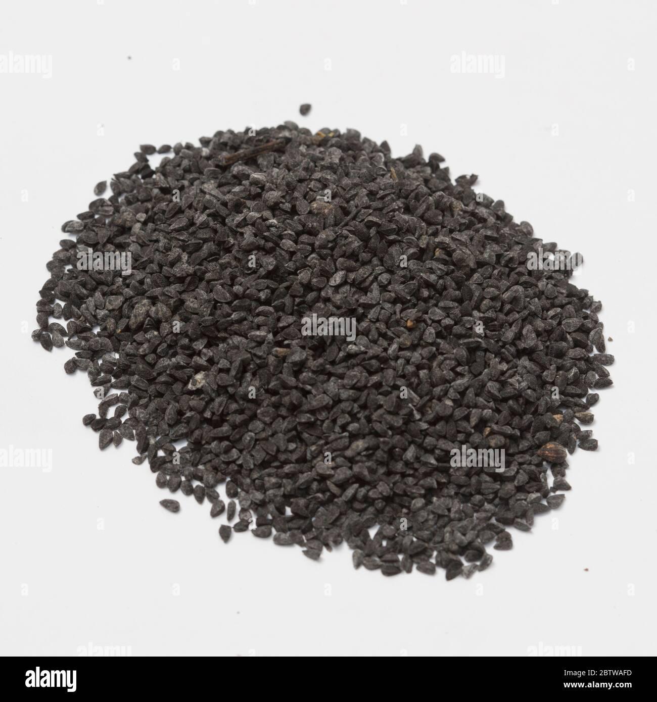 Vue rapprochée du cumin noir brut sur fond blanc. Banque D'Images