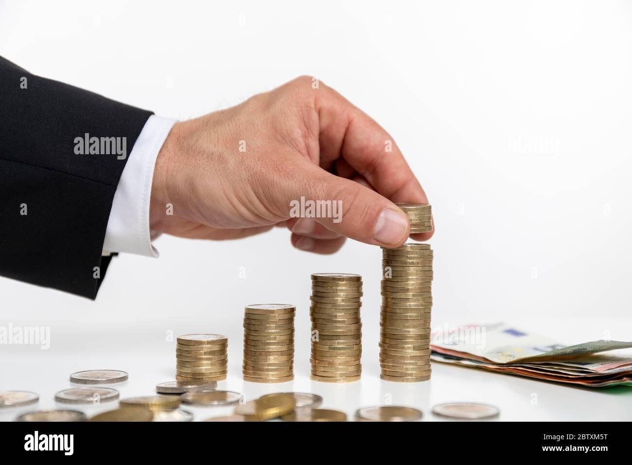 Homme d'affaires à son bureau avec des piles de pièces, Allemagne Banque D'Images