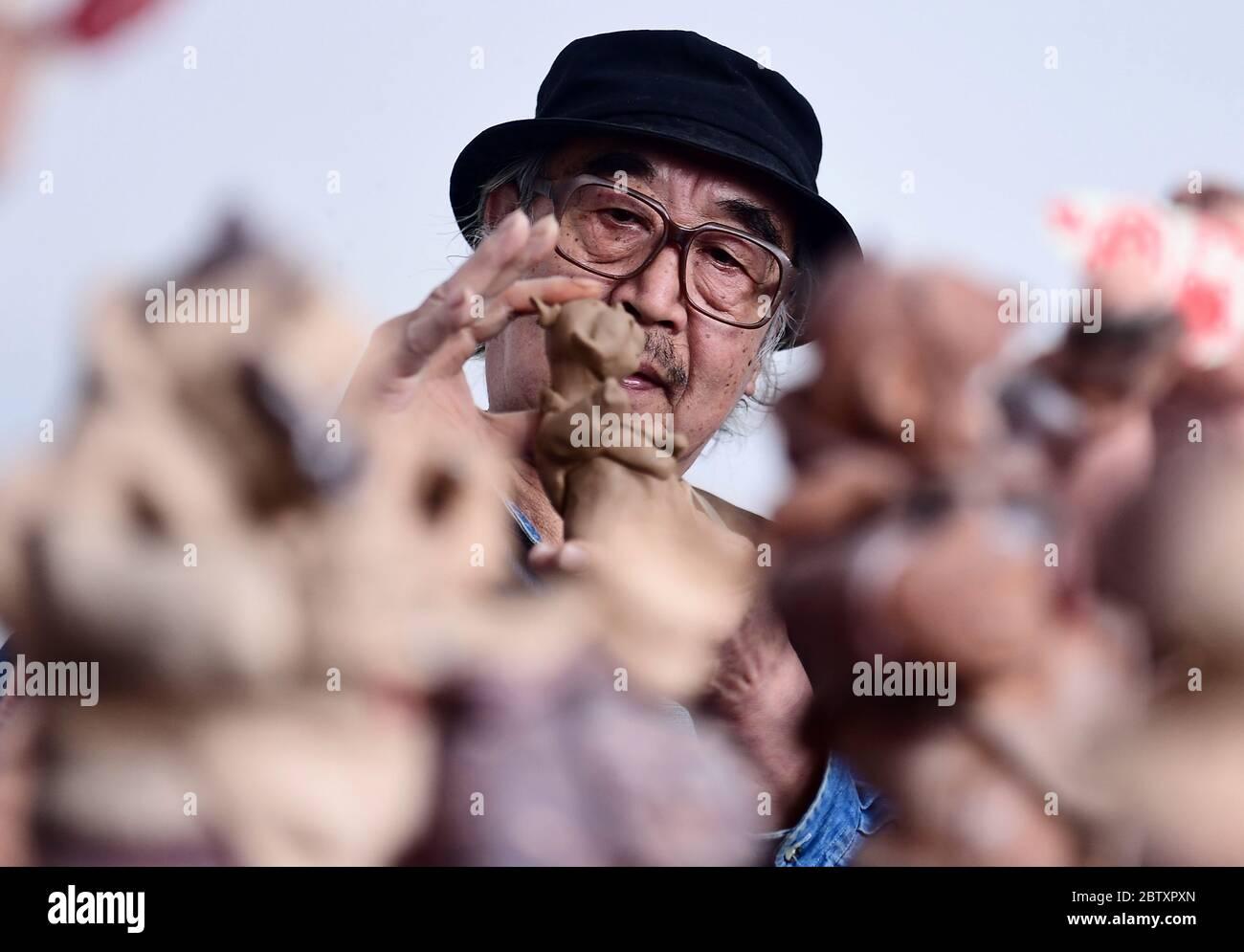 Shenyang, Shenyang, Chine. 28 mai 2020. Liaoningà¯ÂμÅ'CHINA-Wang Chen enseigne aux gens comment pétrir des figurines en argile au musée d'art wang Chen sur la rue changjiang dans la ville de shenyang, province de liaoning, le 24 mai 2020. À peine dix minutes, un morceau de boue commune dans les mains de wang Chen va venir en vie, magasin deux, Bao zi magasin commis, barber, erhu, vendant la gourde glace-sucre. Les petites figures d'argile sont exagérées dans l'apparence et riches dans l'expression, comme si elles reproduissaient les scènes de la vie de marché dans la dynastie qing tardive avec le langage silencieux. (Image crédit: © SIPA Asia via ZUMA Banque D'Images