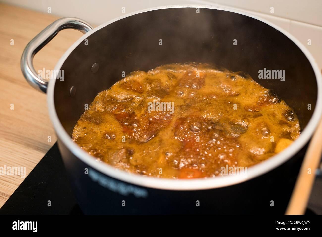 Préparation de la confiture d'abricot dans une casserole noire. Conserver les fruits bouillant dans une grande casserole avec une cuillère en bois. Vue latérale. Banque D'Images
