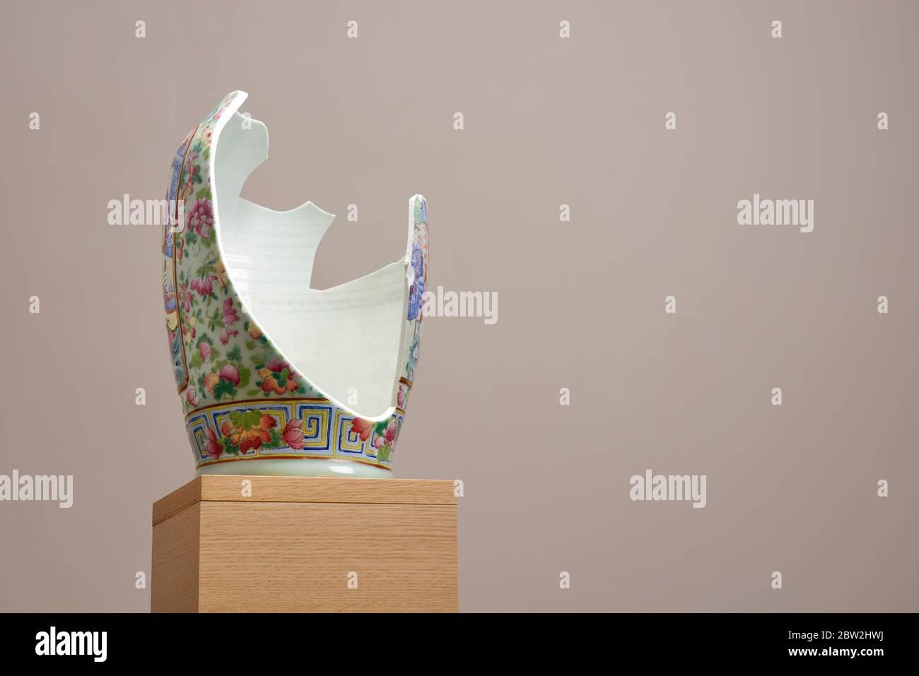 Un vase chinois cassé sur une plinthe en bois Banque D'Images
