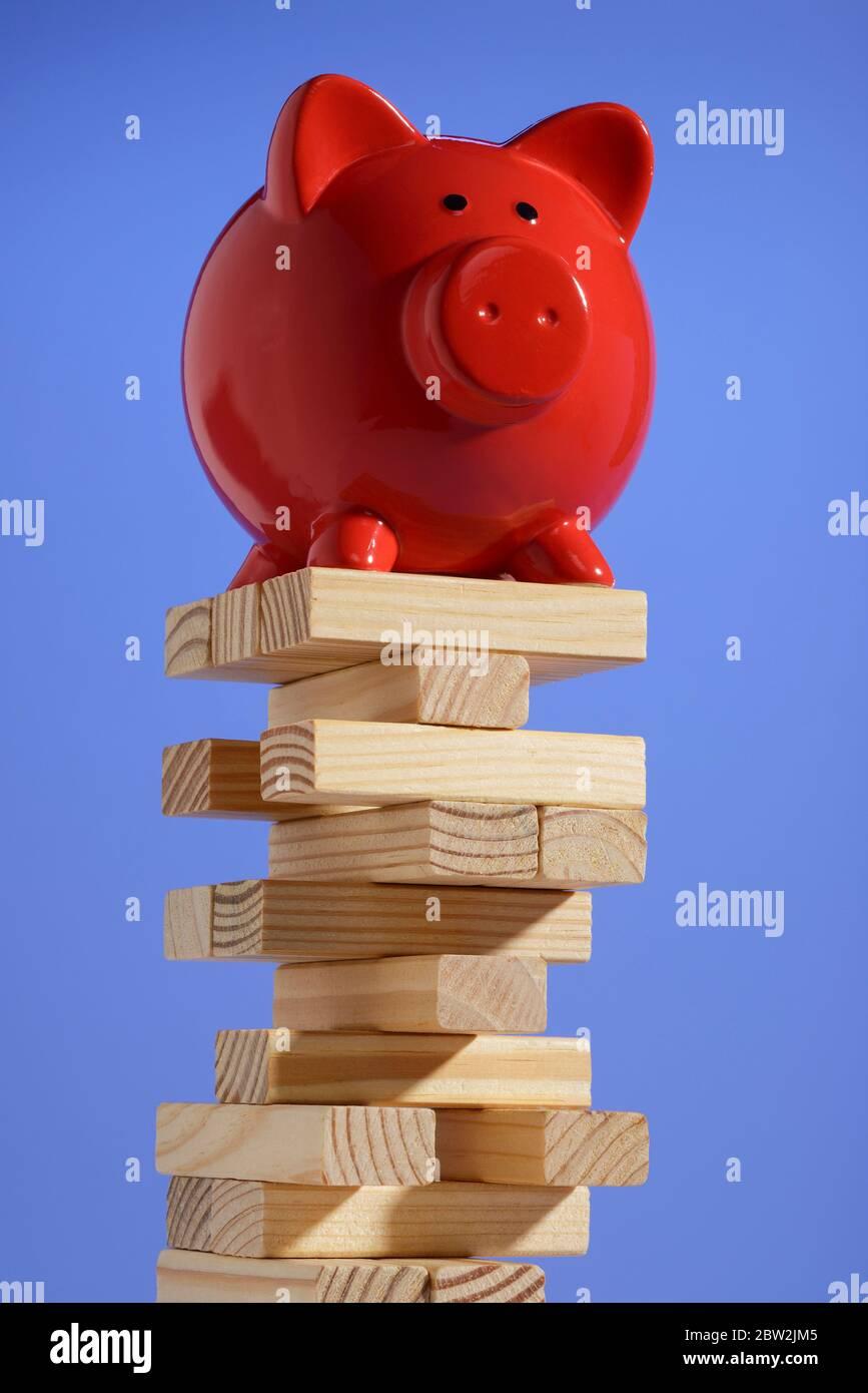 Une tirelire rouge équilibrée sur une pile de blocs de bois Banque D'Images
