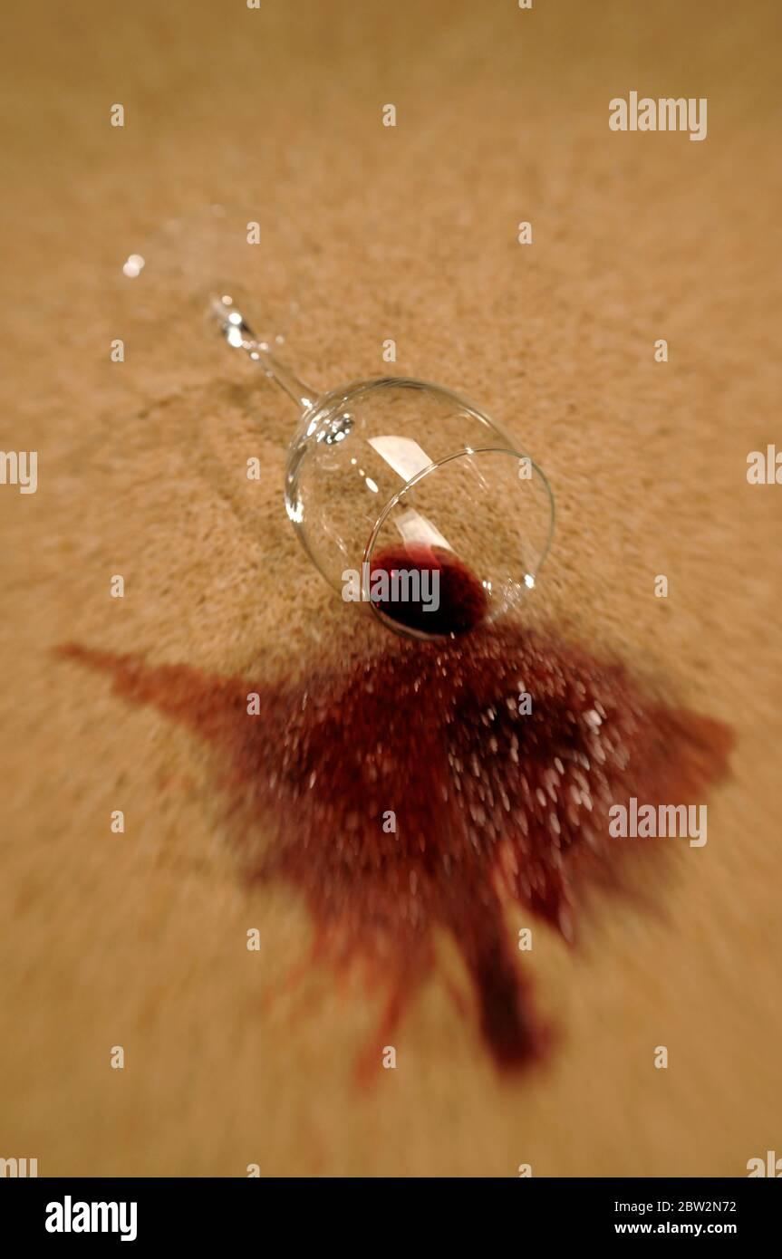 Un verre de vin rouge qui déborde sur un tapis Banque D'Images