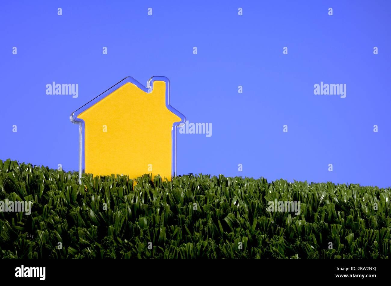 Une forme de maison en plastique jaune sur l'herbe artificielle verte Banque D'Images