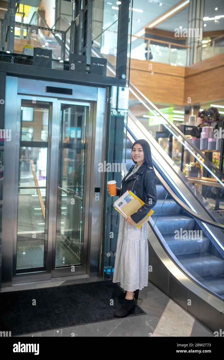 Jeune femme brune debout avec une tasse de café et des papiers près de l'ascenseur, souriant Banque D'Images