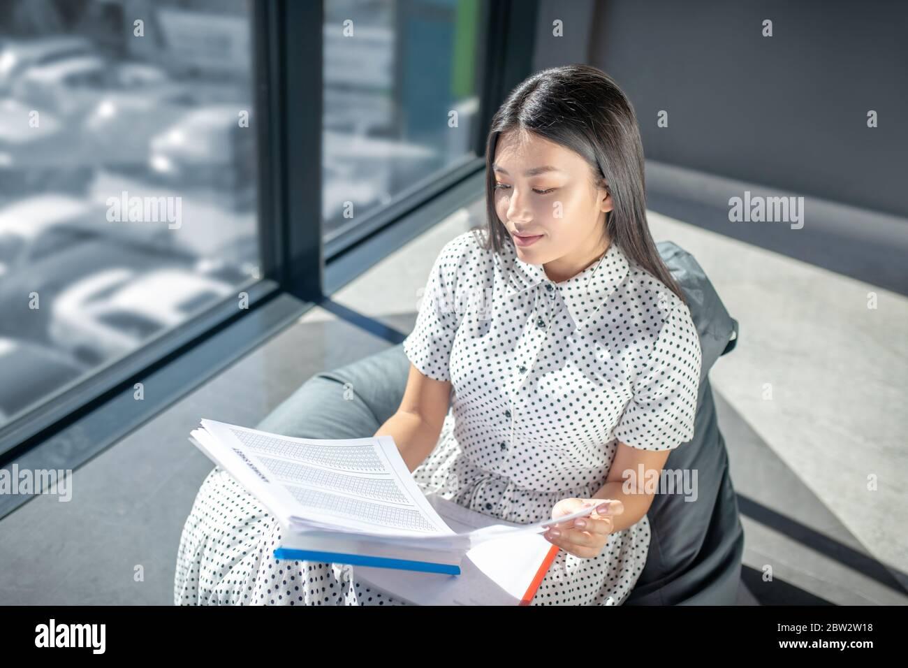 Jeune femme brune assise sur un fauteuil à sac, regardant à travers les papiers, souriant Banque D'Images