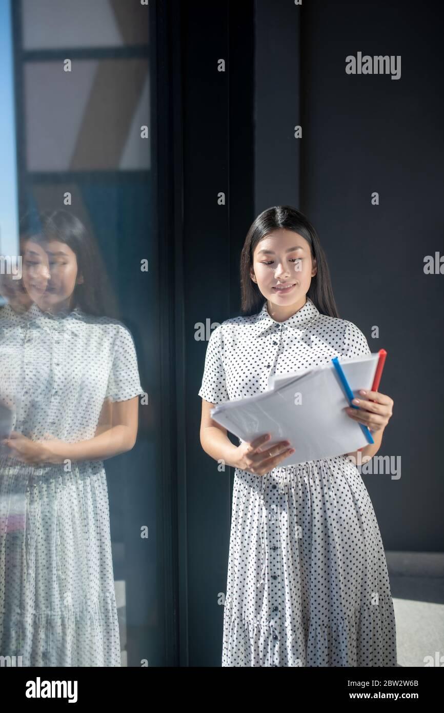 Jeune femme brune debout près de la fenêtre, étudiant des documents, souriant Banque D'Images