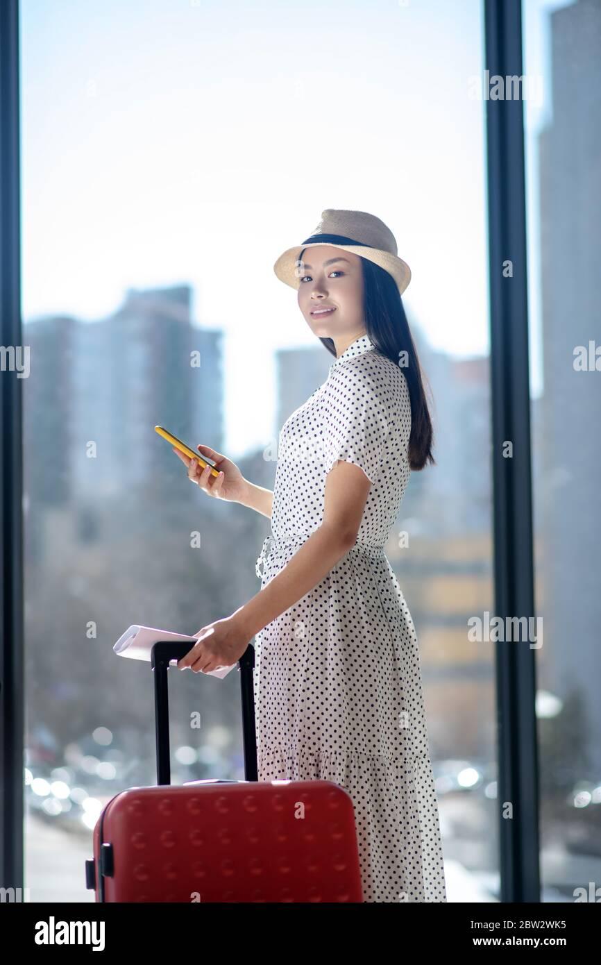 Brunette femme en chapeau de paille debout avec une valise rouge, souriante, tenant son smartphone Banque D'Images