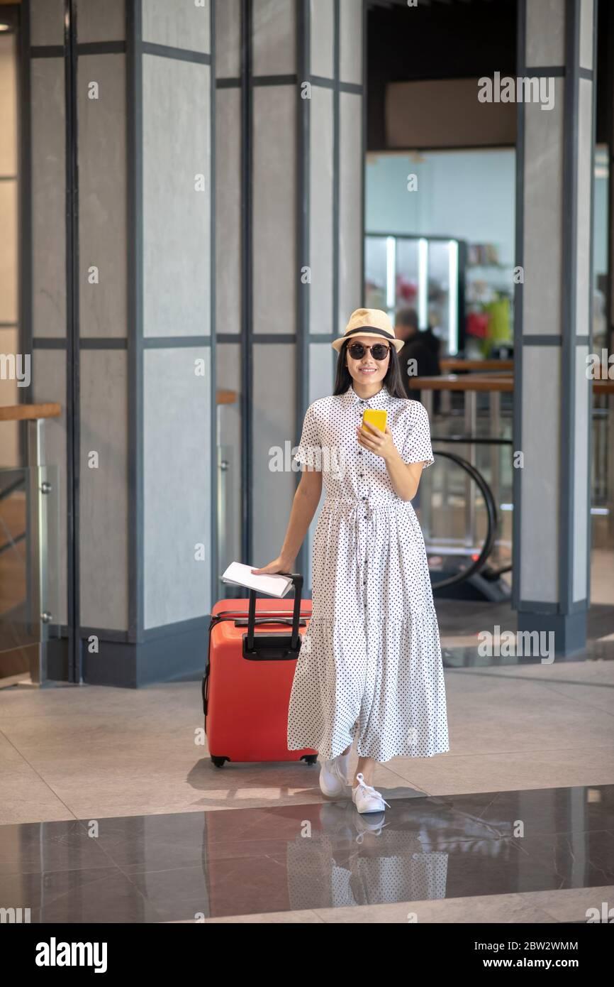 Brunette femme en chapeau de paille et lunettes de soleil marchant avec une valise rouge, vérifiant son smartphone Banque D'Images