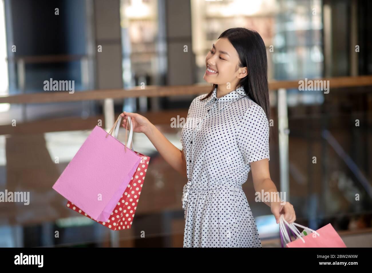 Bonne brune femelle marchant avec des sacs de shopping, beaming Banque D'Images