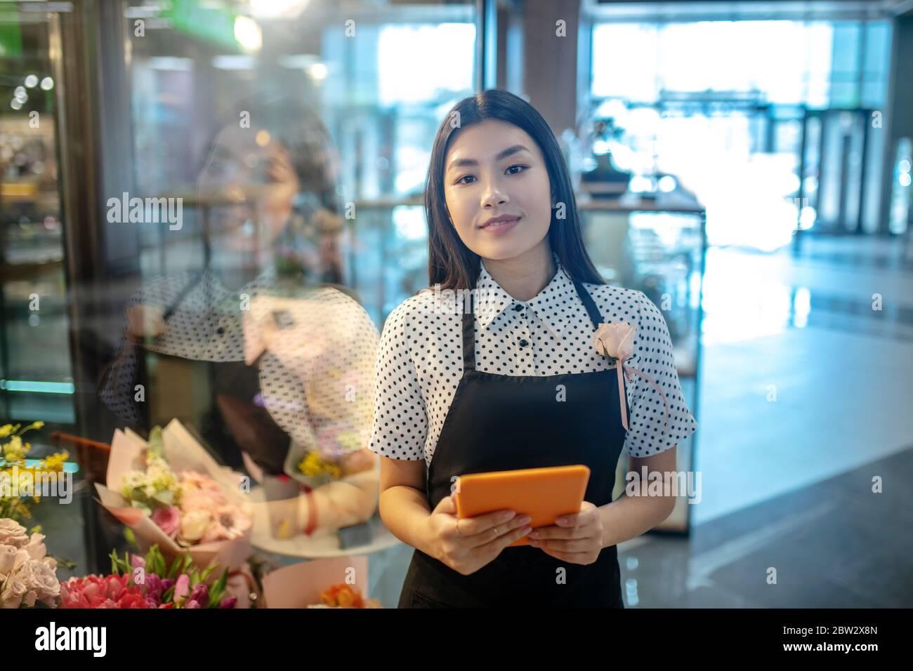 Brunette femme en tablier debout devant les fleurs, tenant sa tablette, souriant Banque D'Images