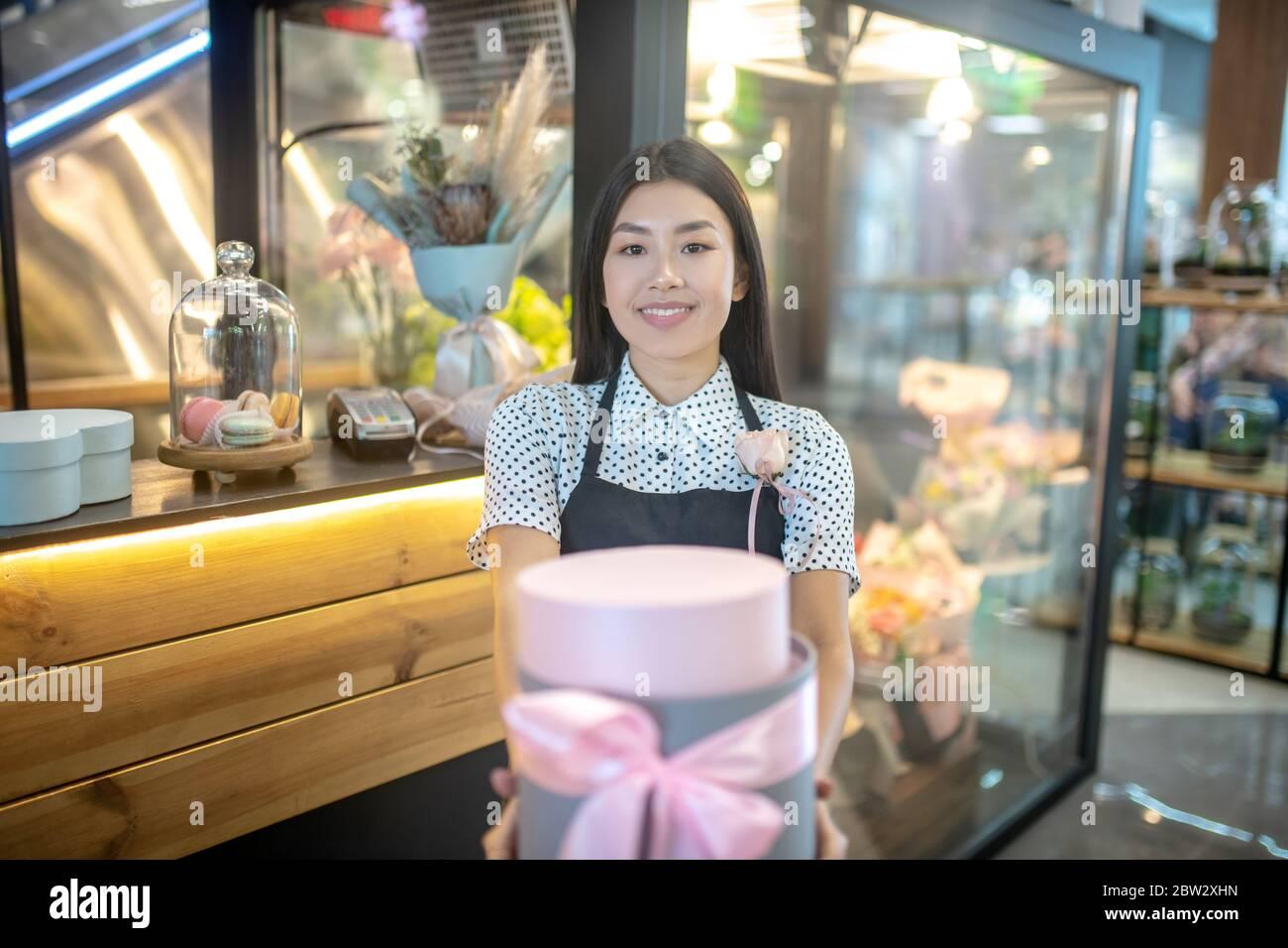Brunette femelle en tablier tenant une boîte cadeau ronde avec noeud rose devant un glacière à fleurs, souriant Banque D'Images