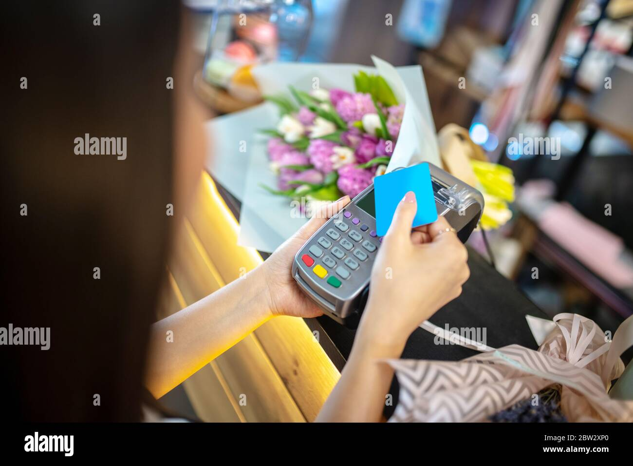Gros plan des mains de femmes tenant la carte de crédit et le terminal de paiement Banque D'Images