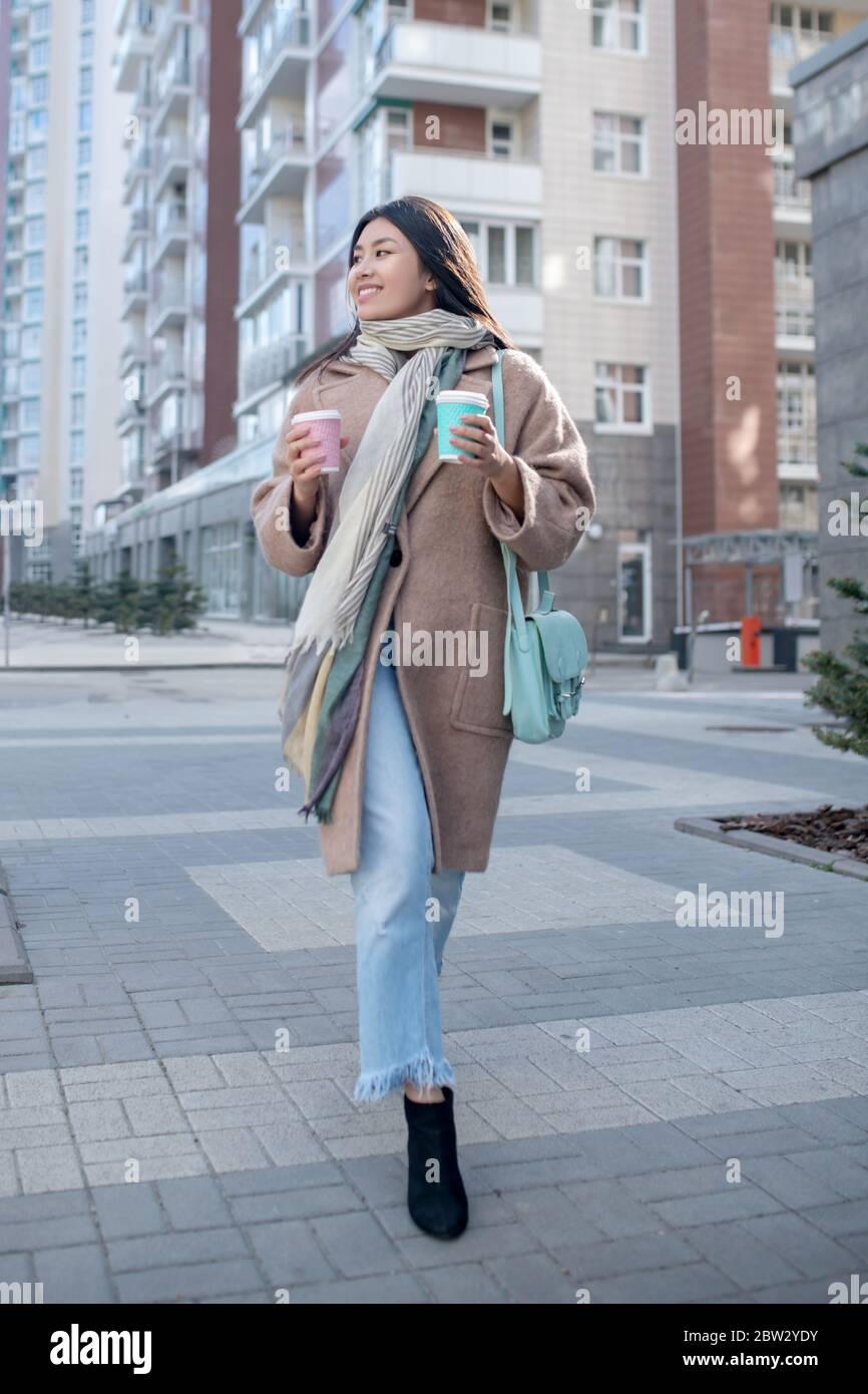 Brunette femme au pelage beige tenant une tasse de café, appréciant sa boisson, marchant le long de la rue Banque D'Images