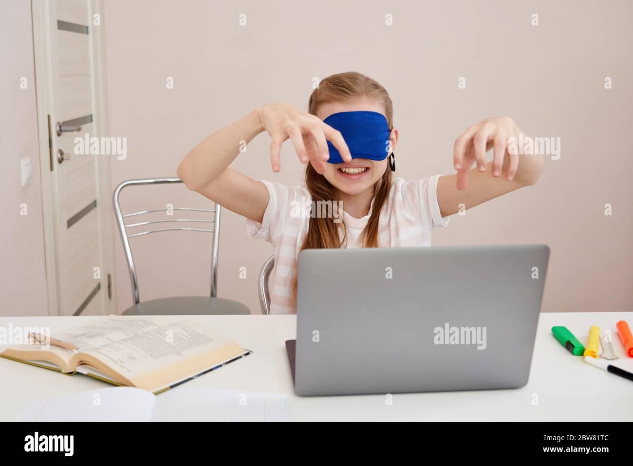 jeune fille en colère apprenant le toucher dactylographiant sur le clavier, la fille est dactylographiée avec les yeux fermés portant le masque de sommeil Banque D'Images
