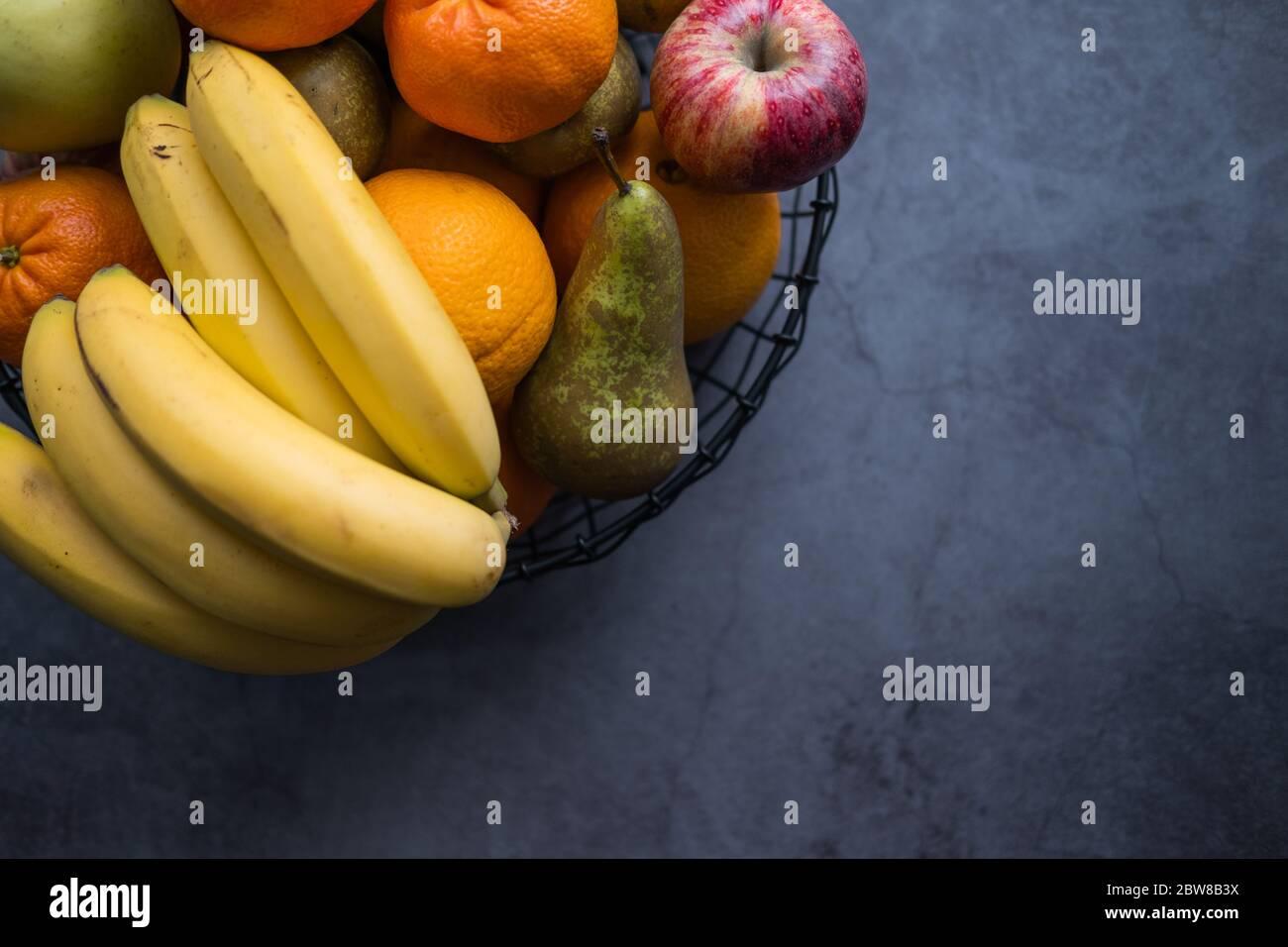 Pommes, bananes, poires, mandarines et oranges sur un bol de fruits sur fond de béton. Une alimentation saine. Vue de dessus. Copier l'espace. Banque D'Images