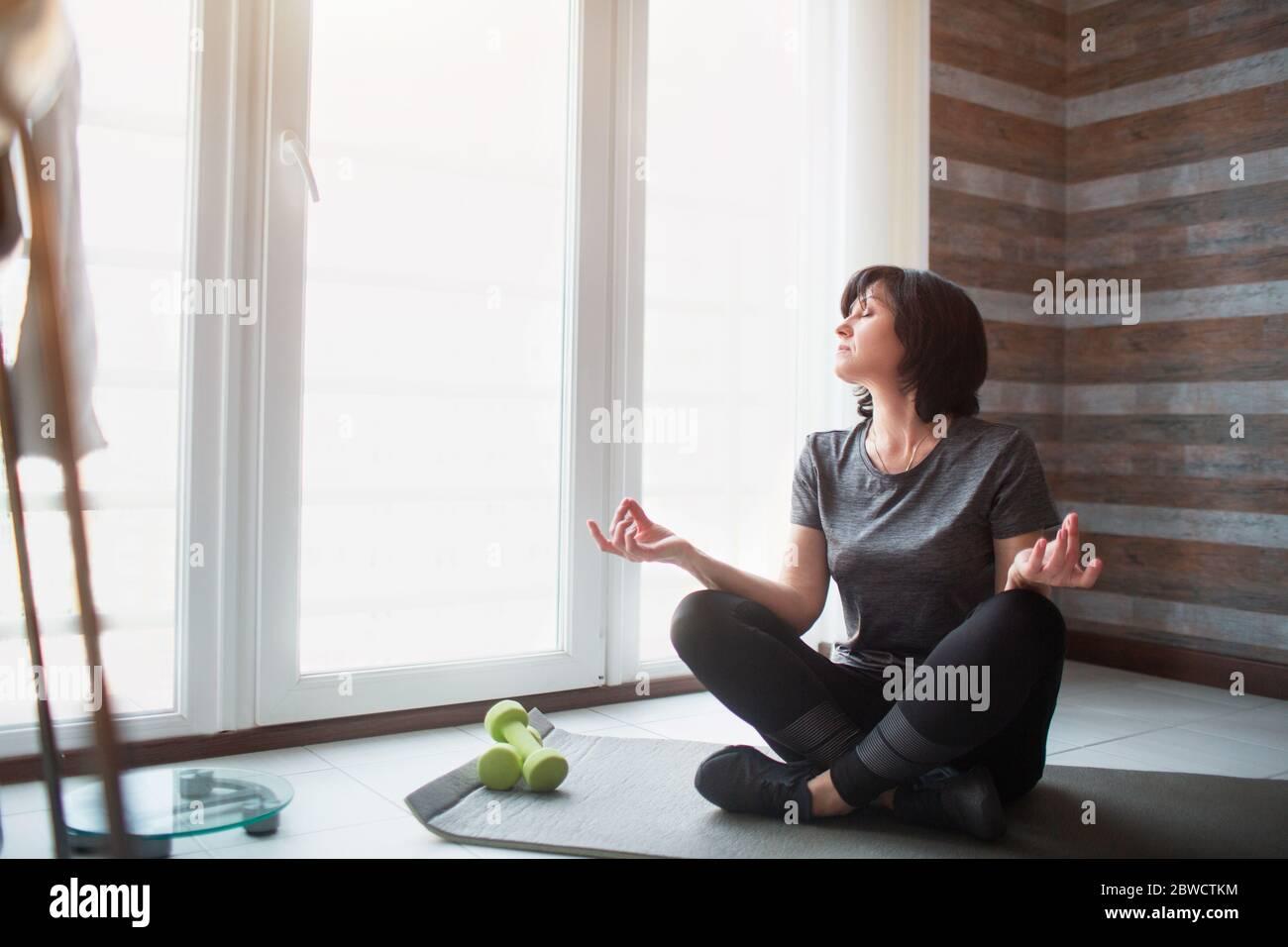La femme fine pour adulte s'entraîner à la maison. Processus de méditation du modèle senior. Tenez les mains sur les genoux et regardez la fenêtre. Banque D'Images