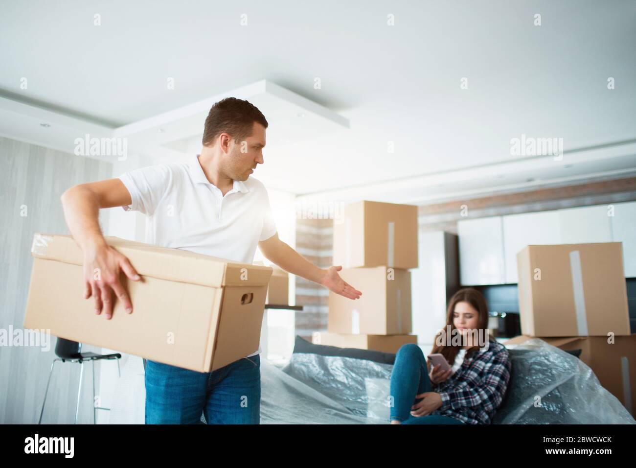 Concept de déplacement et de relation. Il n'est pas satisfait. Le mari déboîte les boîtes. Et la femme ne fait rien pendant ce temps. Elle préfère lui parler Banque D'Images