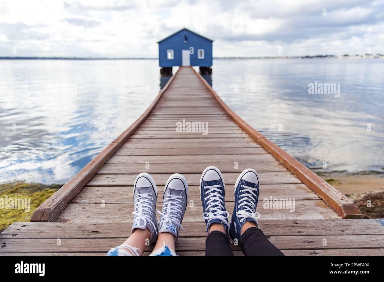 Perth, novembre 2019 : couple touristique portant des baskets profitant de la vue sur la maison de bateau bleue - le hangar de bateau Crawley Edge situé sur la rivière Swan à Perth. Banque D'Images
