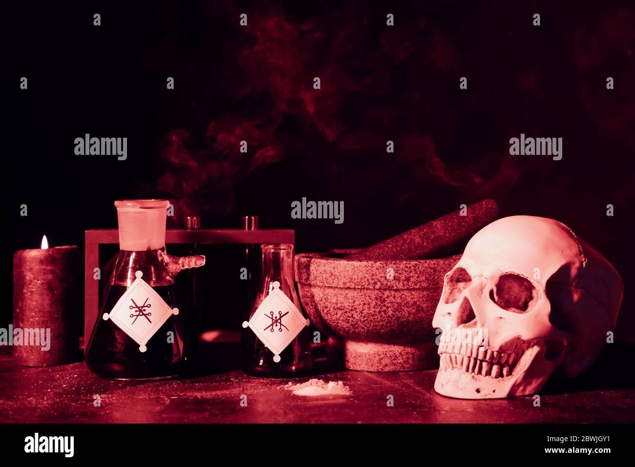 Potions, crâne humain, mortier et pilon sur la table de l'alchimiste Banque D'Images