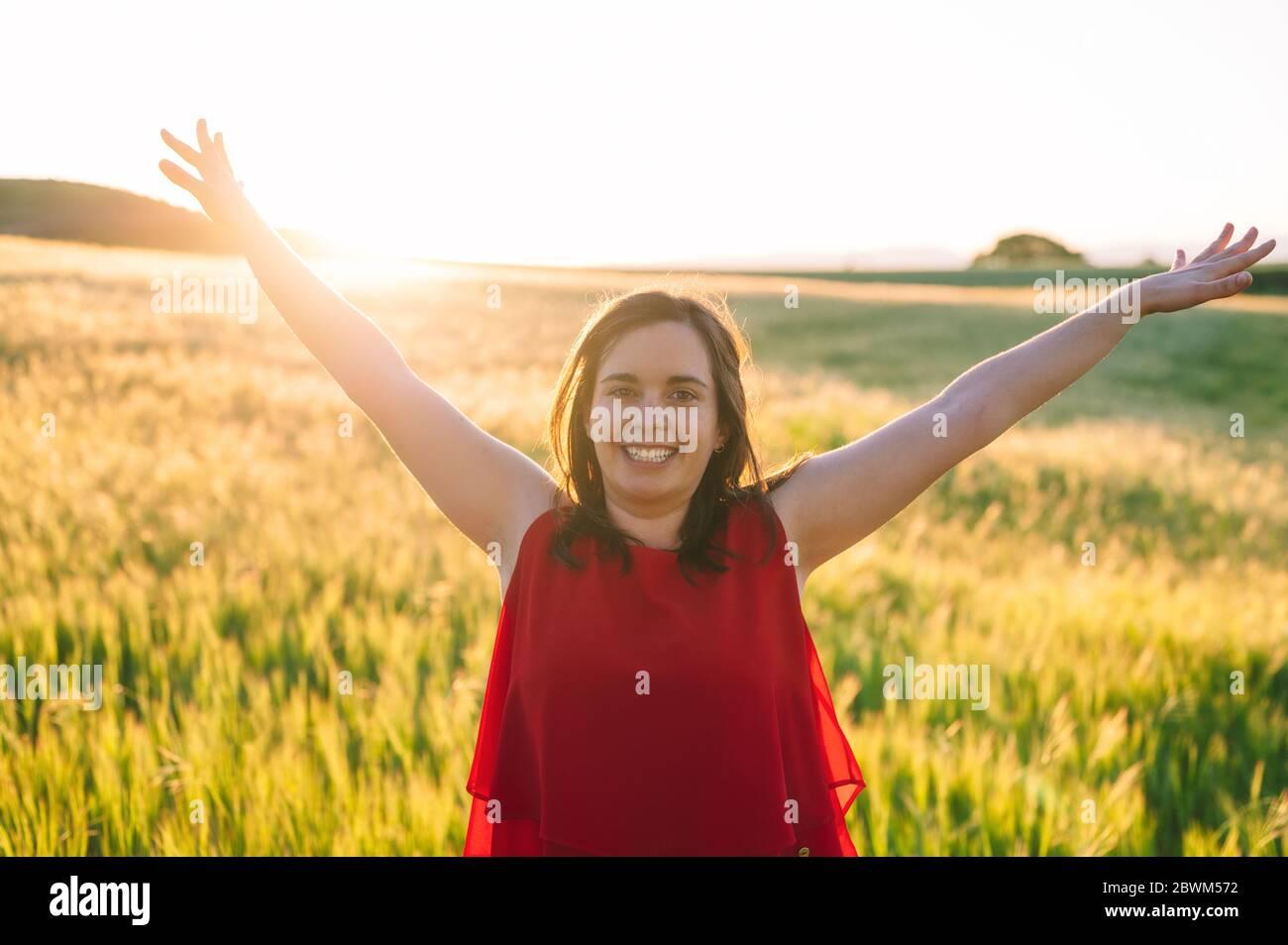 Les jeunes femmes sont soulevées jusqu'au ciel, célébrant la liberté. Émotions positives sentir la vie perception succès, paix de l'esprit concept. Fille heureuse gratuite dans un pré d'été profitant du coucher de soleil dans la nature . Banque D'Images